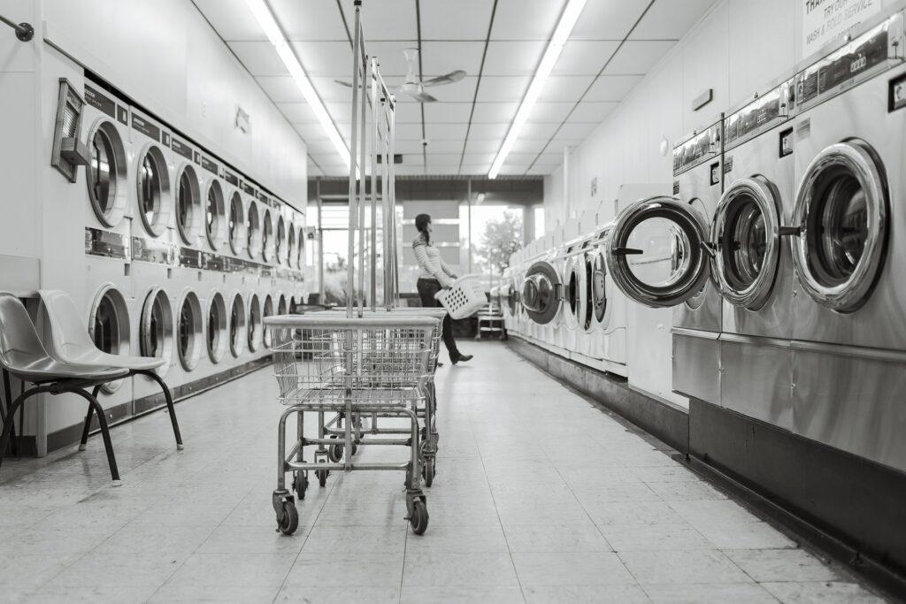 Bild zeigt einen Waschsalon in schwarz weiß. Links und rechts sind Maschienen aufgereit. Ind er Mitte der Gang mit fahrbaren Waschkörben